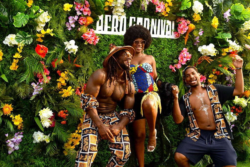 Models Kyron Green (left) and Jaime Pamplin (right) pose for photographers in clothing designed by the owner of Eldior Sodeck,  Marianne Sodogandji (center).
