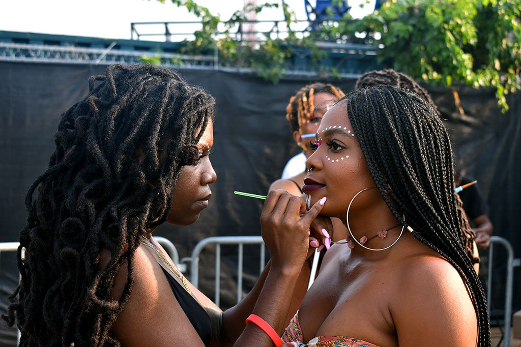 A second face painter adds detailed touches to a festival attendee who holds perfectly still to the side of a growing crowd.