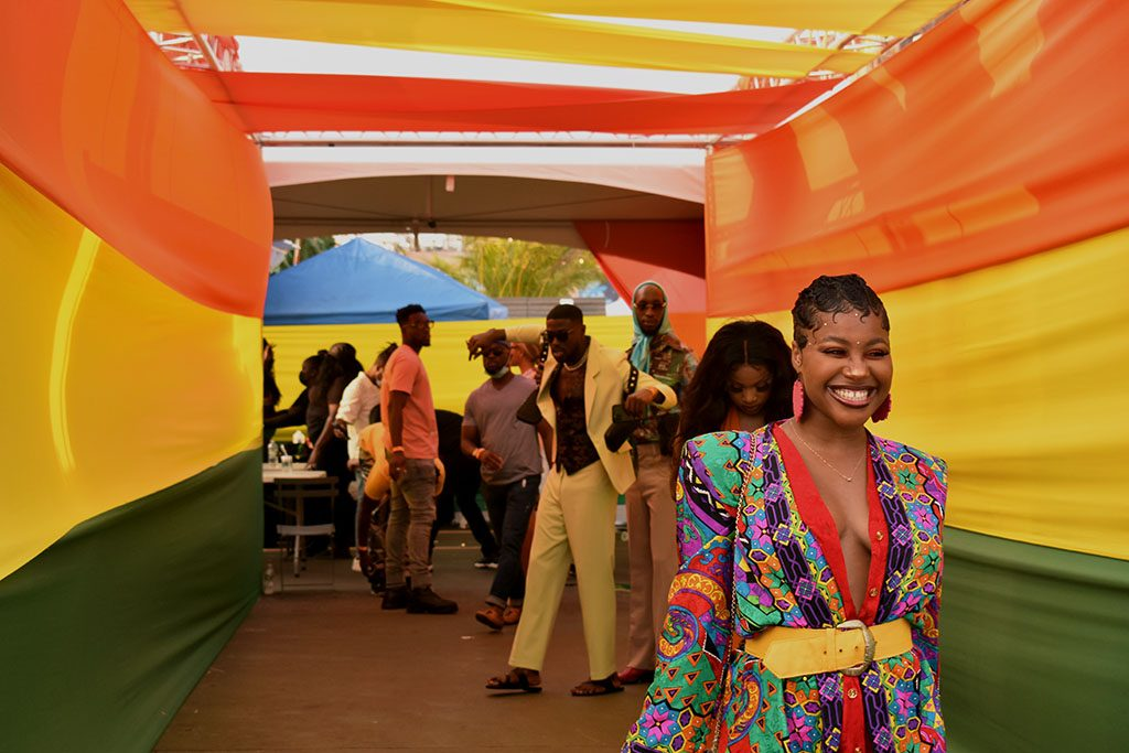 Festival goers stream into Afro Carnival with smiles as bright as their styles.